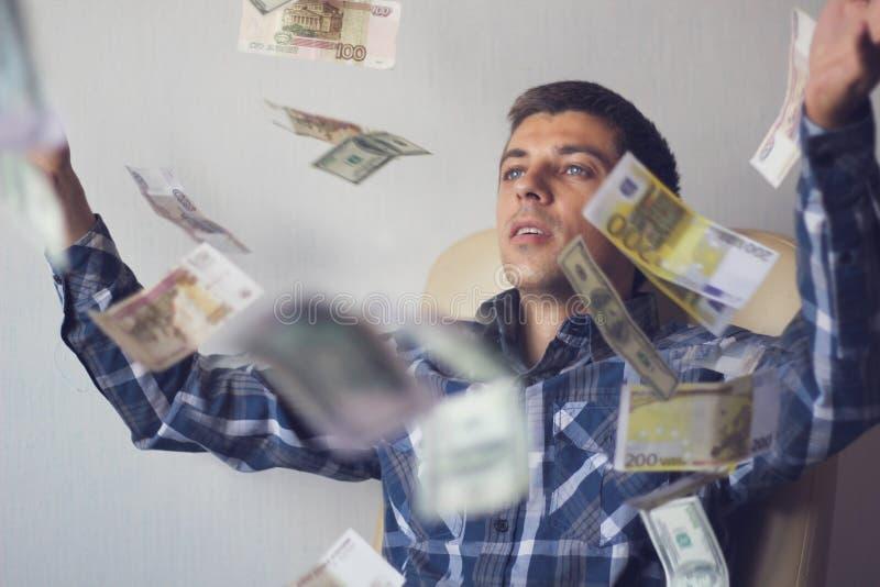 Jonge mensenzakenman onder vliegende bankbiljetten stock afbeelding
