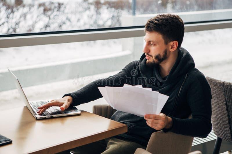 Jonge mensenzitting bij de koffie en het gebruiken van laptop stock afbeelding