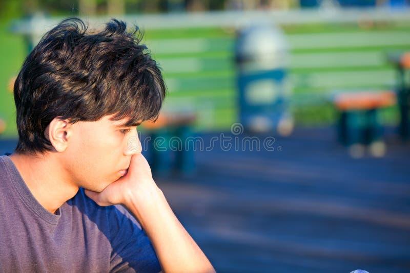 Jonge mensenzitting bij park, diep in gedachte royalty-vrije stock afbeeldingen