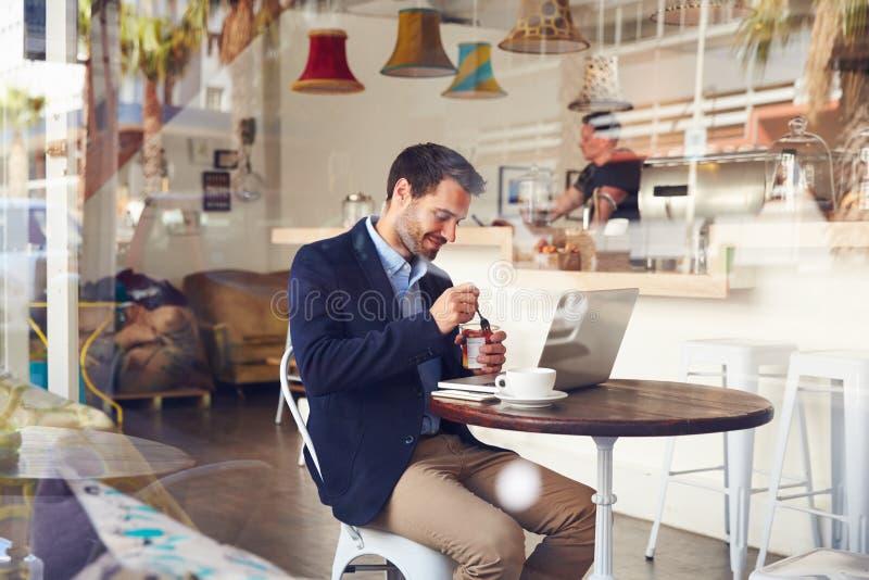 Jonge mensenzitting in een koffie die een dessert eten royalty-vrije stock afbeelding