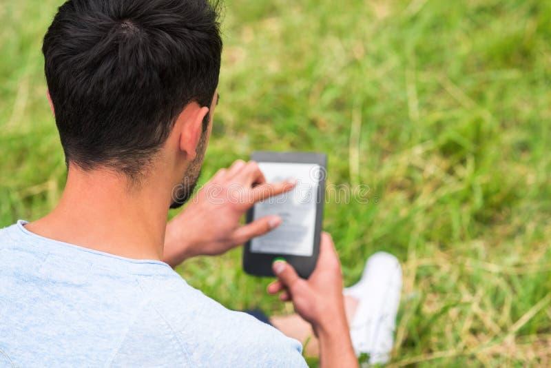 Jonge mensenzitting in het groene gras en het gebruiken van tablet op groen gras royalty-vrije stock foto's
