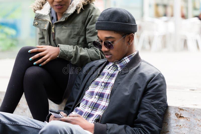 Jonge mensenzitting met zijn meisje mobiel gebruiken stock afbeelding