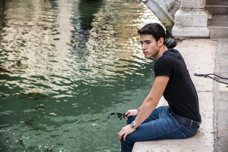 Jonge Mensenzitting naast Kanaal in Venetië, Italië stock afbeelding
