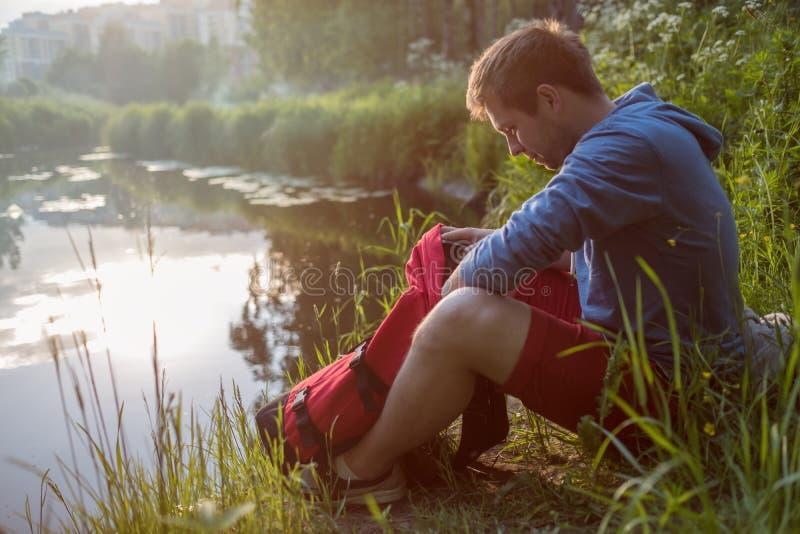 Jonge mensenzitting naast rivier en het genieten van in zonnige dag royalty-vrije stock fotografie