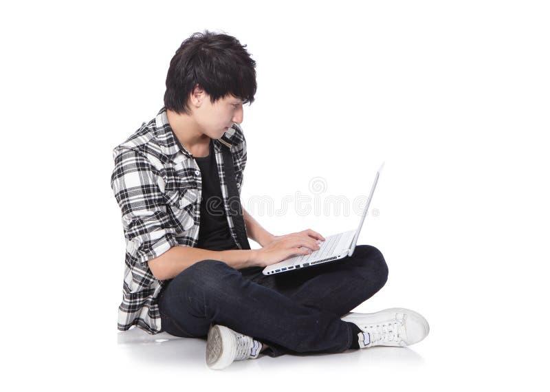 Jonge mensenzitting op de vloer met laptop royalty-vrije stock fotografie