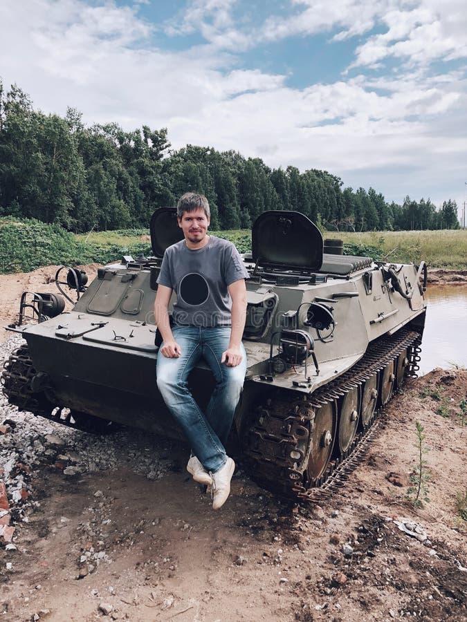 Jonge mensenzitting op een militaire tank stock foto