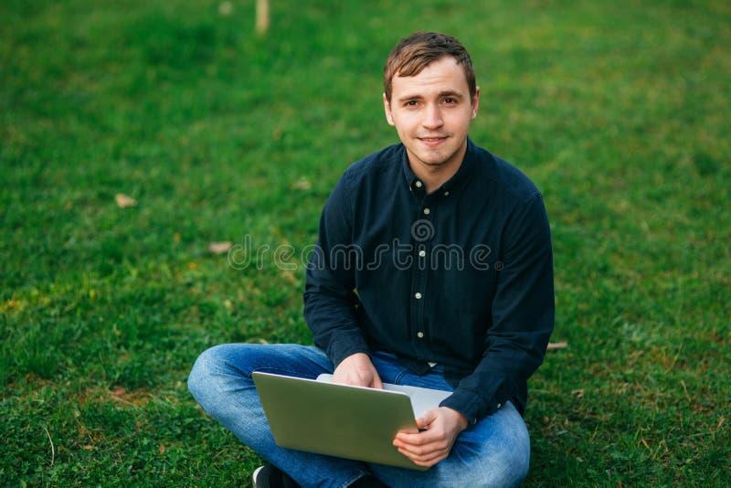Jonge mensenzitting op het gras in het park en het werk aangaande laptop royalty-vrije stock afbeeldingen