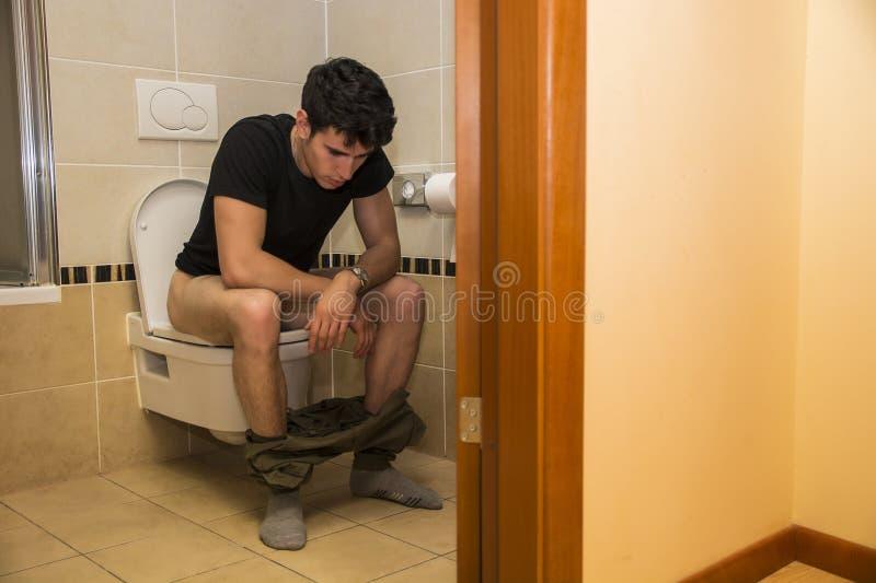 Jonge Mensenzitting op Toilet stock fotografie