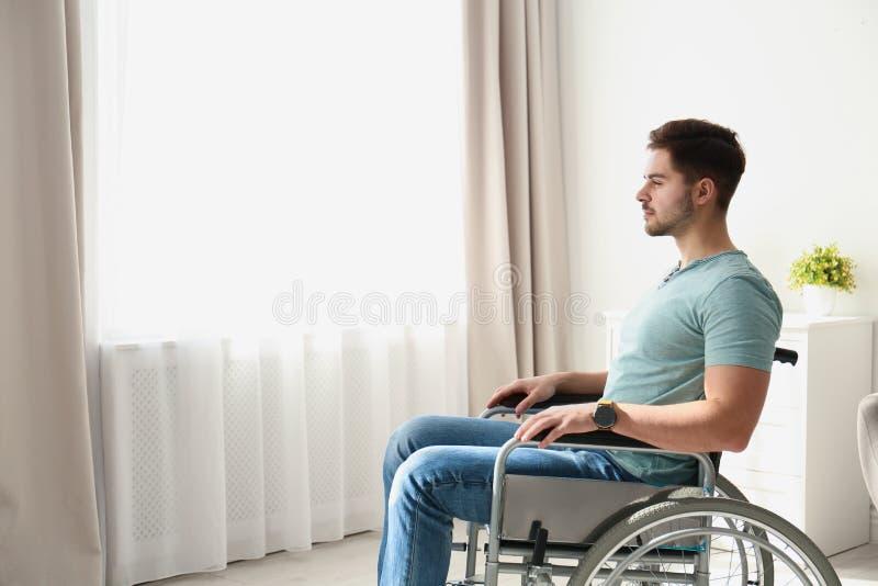 Jonge mensenzitting in rolstoel dichtbij venster binnen stock fotografie