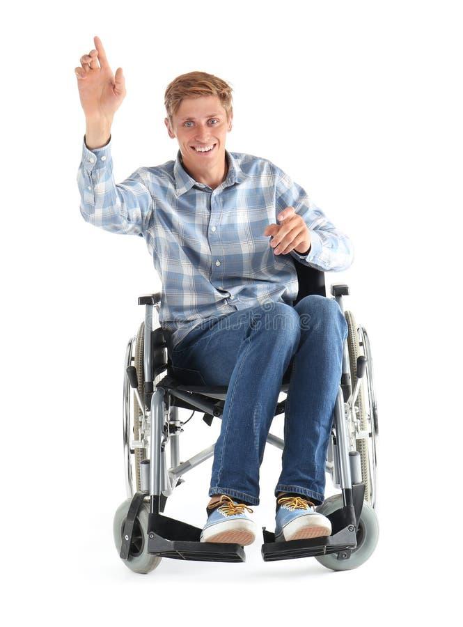 Jonge mensenzitting in rolstoel op witte achtergrond royalty-vrije stock fotografie