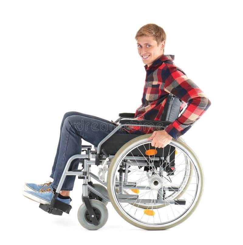 Jonge mensenzitting in rolstoel op witte achtergrond stock afbeelding