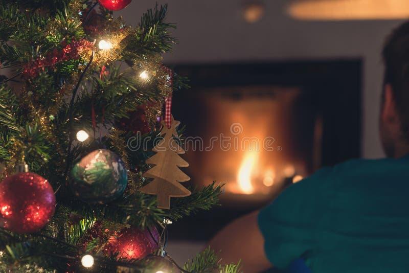 Jonge mensenzitting voor brandplaats voor Kerstmis royalty-vrije stock foto's