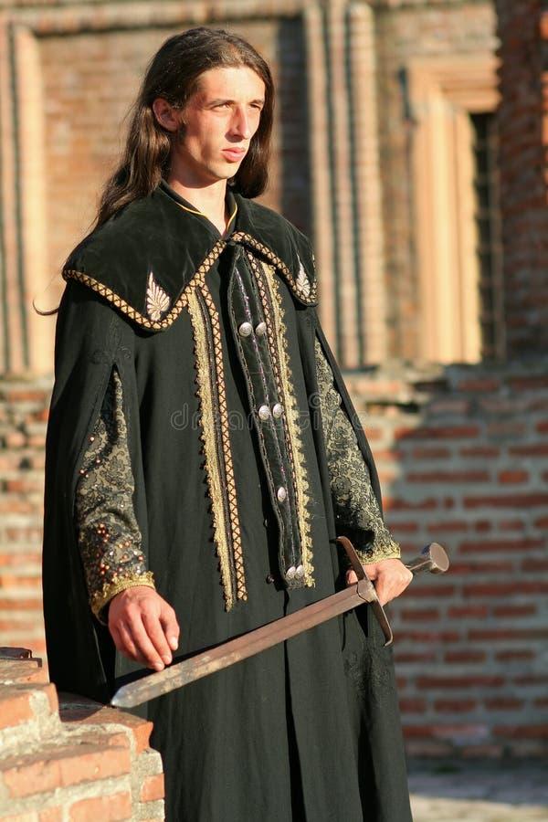 Jonge middeleeuwse prins met sabel en zwarte mantel stock afbeelding
