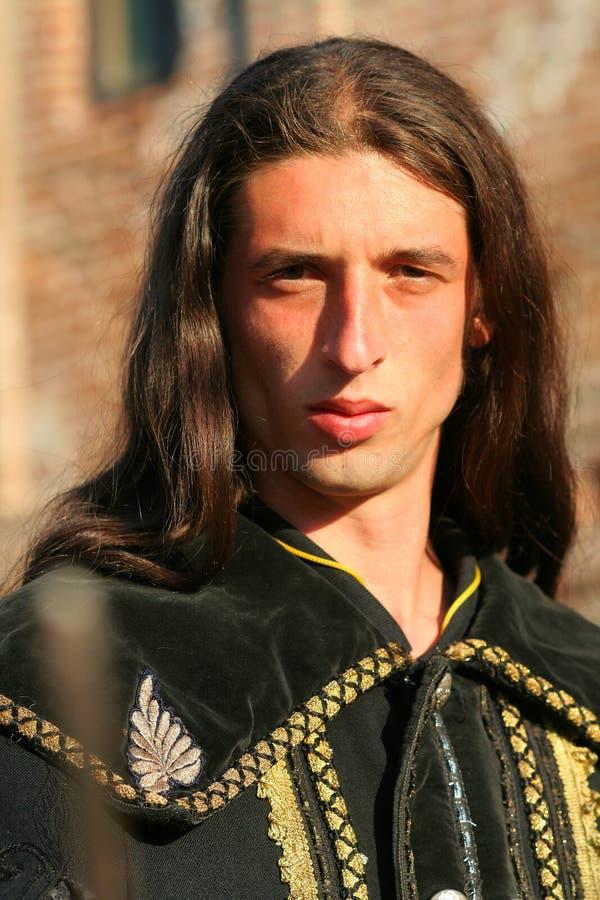 Jonge middeleeuwse prins met sabel en zwarte mantel stock foto