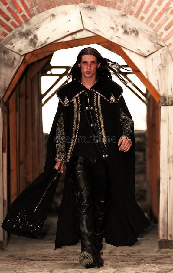 Jonge middeleeuwse prins met sabel en zwarte mantel stock afbeeldingen