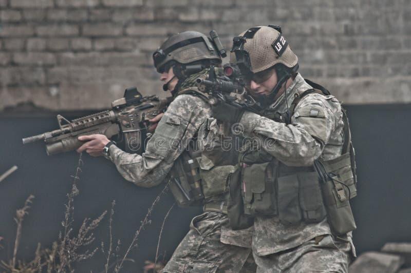 Jonge militairen op patrouille in rook stock fotografie