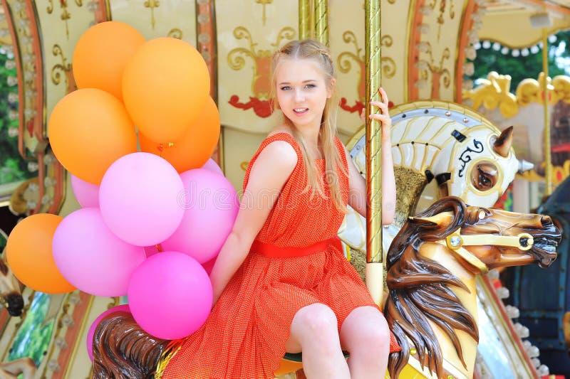 Jonge modelvrouw die een carrousel berijden royalty-vrije stock foto's