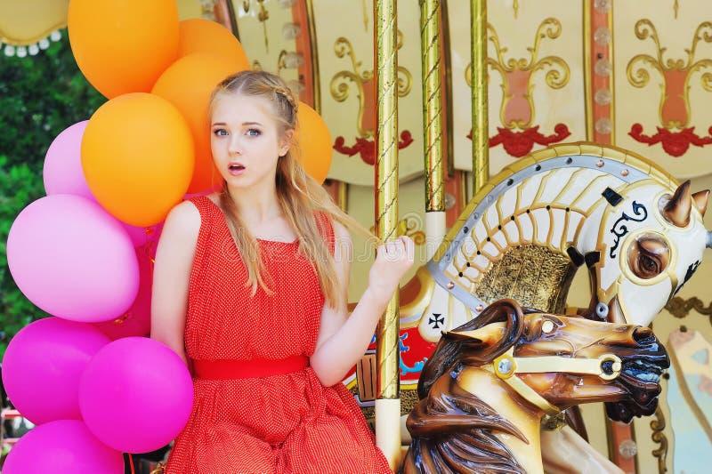 Jonge modelvrouw die een carrousel berijden stock fotografie