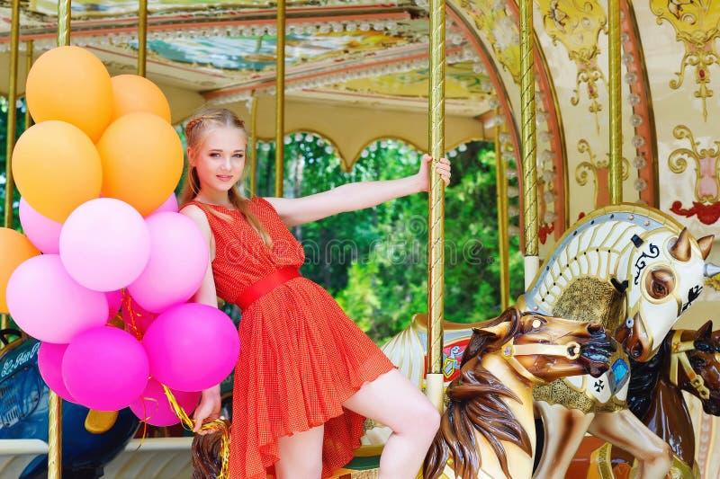 Jonge modelvrouw die een carrousel berijden royalty-vrije stock afbeelding