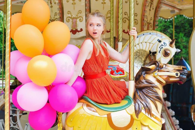 Jonge modelvrouw die een carrousel berijden stock foto's