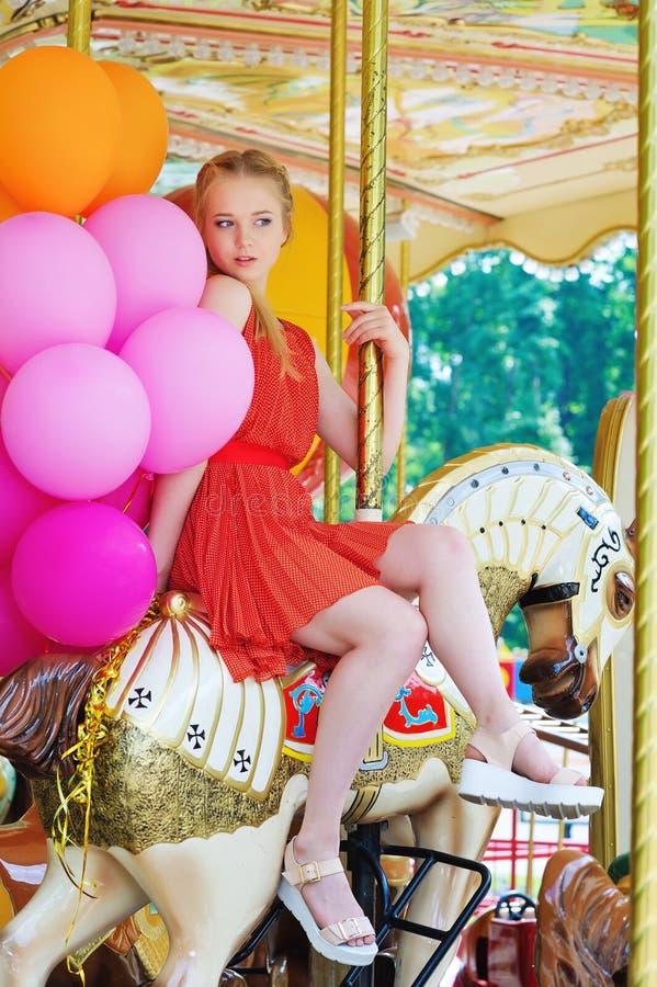 Jonge modelvrouw die een carrousel berijden stock foto