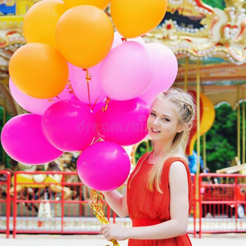 Jonge modelvrouw die met kleurrijke ballons glimlachen stock foto