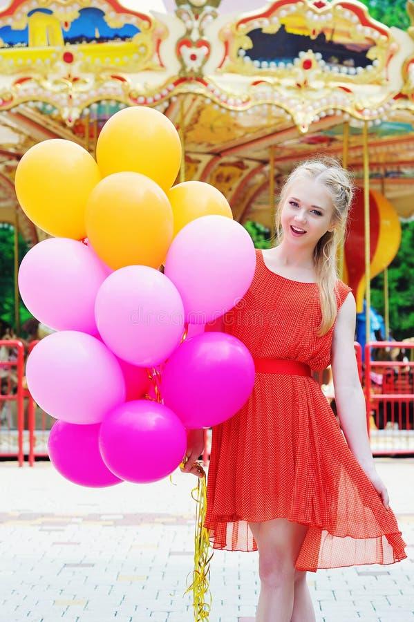 Jonge modelvrouw die met kleurrijke ballons glimlachen royalty-vrije stock foto