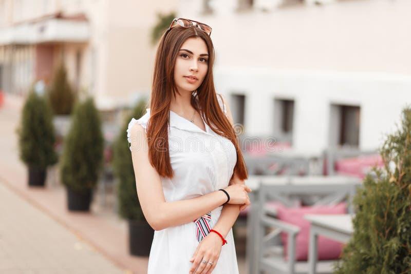Jonge modelvrouw in witte modieuze kleding in de stad stock foto's