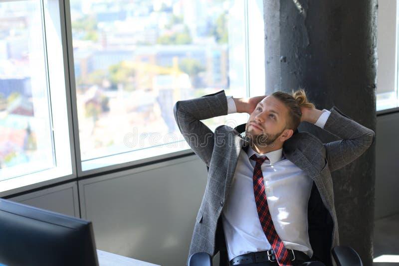 Jonge moderne handen achter hoofd houden en zakenman die terwijl het zitten in het bureau glimlachen stock afbeelding