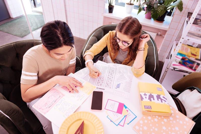 Jonge moderne slimme studenten die in weinig comfortabele koffie werken stock foto's