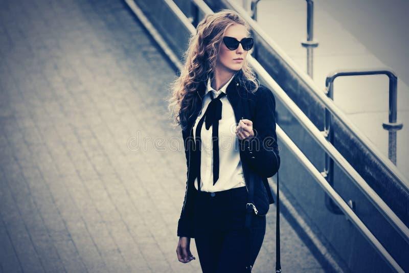 Jonge modezakenvrouw in zonnebril op straat stock foto