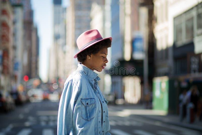 Jonge modieuze Afrikaanse Amerikaanse vrouw die de straat kruisen royalty-vrije stock foto