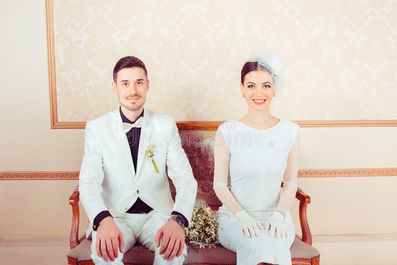 Jonge modieuze bruid en bruidegom op bank royalty-vrije stock foto's