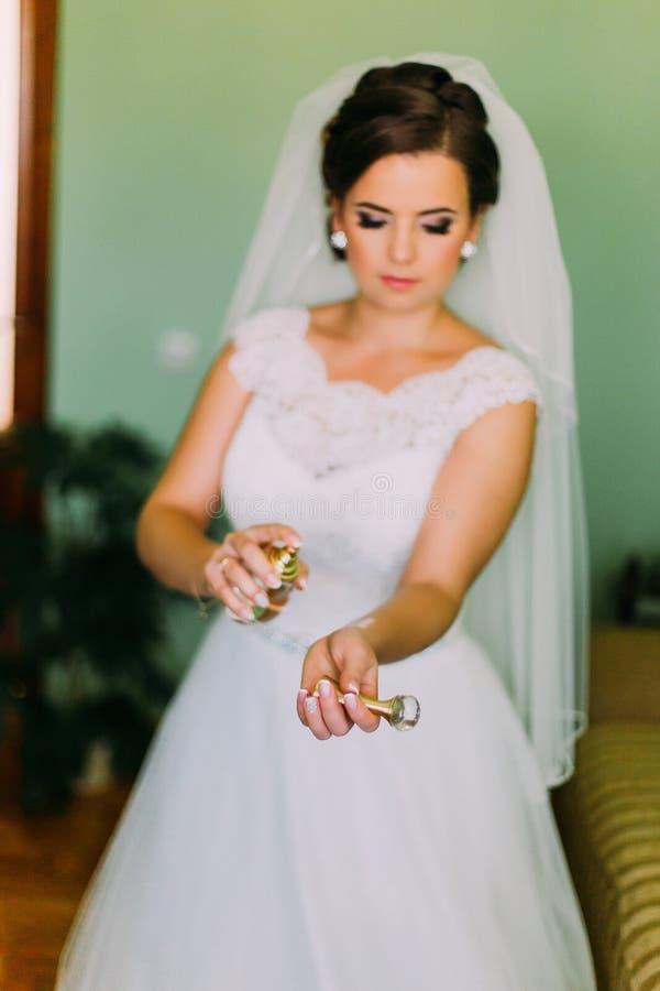 Jonge modieuze bruid in schitterende witte kleding die parfum op haar handen gebruiken stock foto