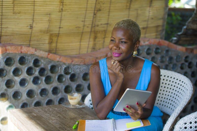 Jonge modieuze en elegante zwarte Afrikaanse Amerikaanse bedrijfsvrouw die bij in koffiewinkel werken die digitaal tabletstootkus stock afbeeldingen