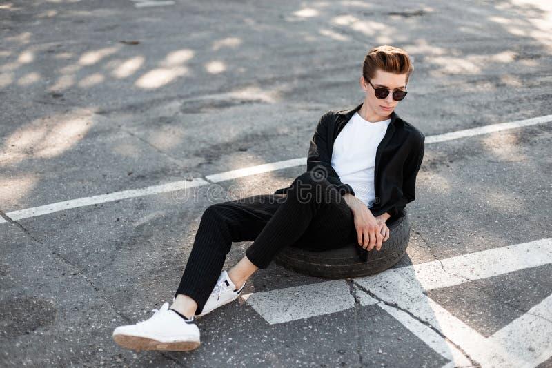 Jonge modieuze hipstermens met in kapsel in een elegant zwart overhemd in gestreepte broek in het witte tennisschoenen zitten royalty-vrije stock foto