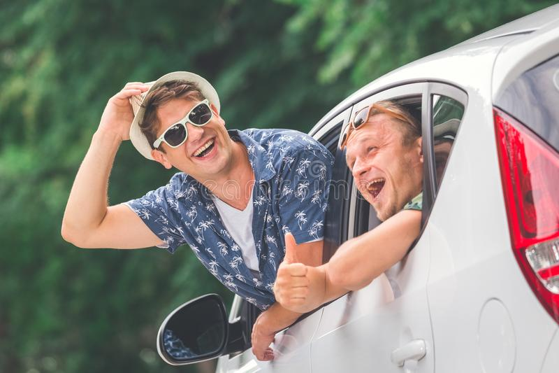 Jonge modieuze hipsters uit autoramen gelukkig om op reis samen te gaan stock foto