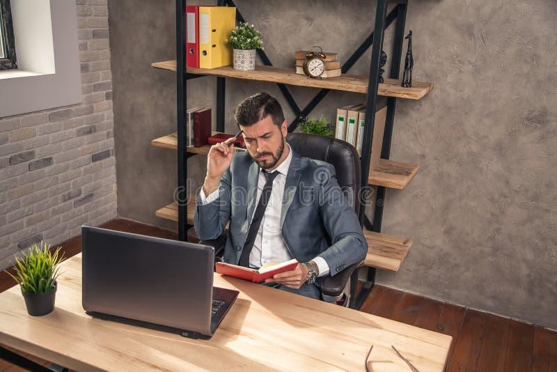 Jonge modieuze knappe zakenman die in het bureau bij zijn bureau werken die wat nota's het denken maken stock afbeelding