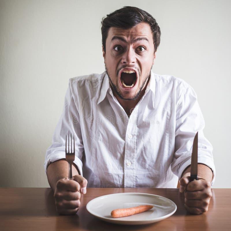 Jonge modieuze mens die met wit overhemd wortel eten royalty-vrije stock foto's
