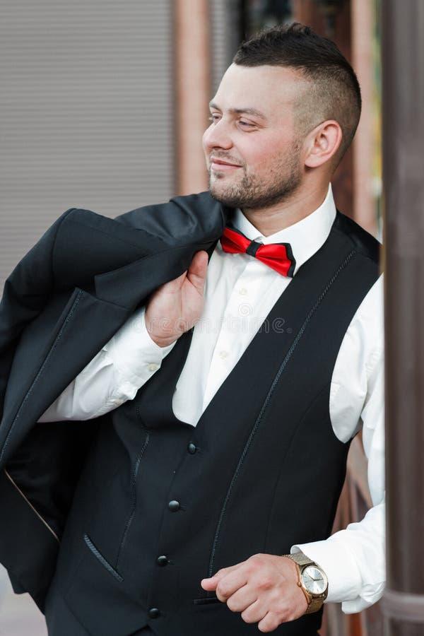 Jonge modieuze mens in een kostuum Portret van de bruidegom De bruidegom houdt zijn jasje op zijn schouder, zijaanzicht royalty-vrije stock fotografie