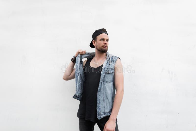 Jonge modieuze mens in een zwart GLB in een modieus denimvest in een T-shirt in zwarte jeans met baard het stellen dichtbij een w royalty-vrije stock afbeelding