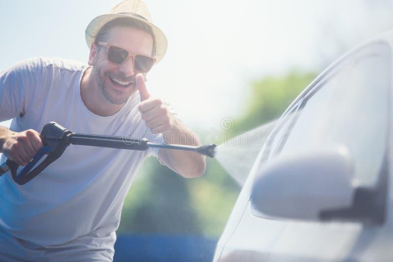 Jonge modieuze mens met hoed en zonnebril die duimen tonen en auto met onder druk gezet water in autowasserette wassen royalty-vrije stock foto's