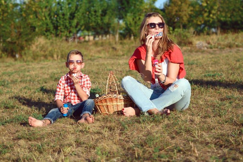Jonge modieuze moeder blazende zeepbels met haar weinig leuke zoonszitting op het gras royalty-vrije stock afbeelding