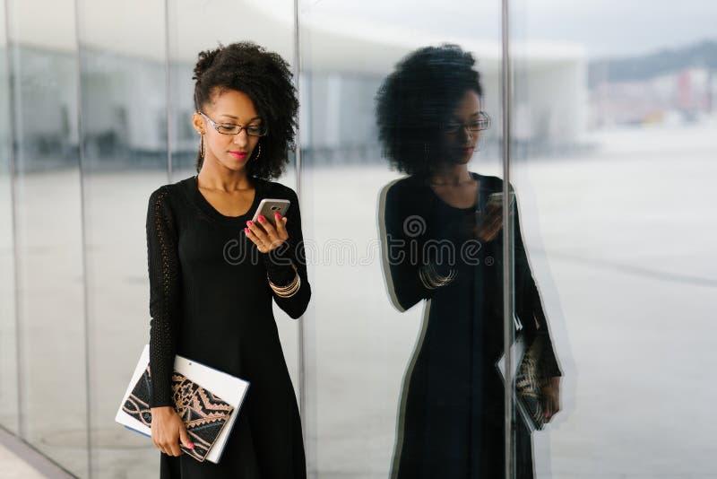 Jonge modieuze onderneemster die cellphone gebruiken stock afbeeldingen