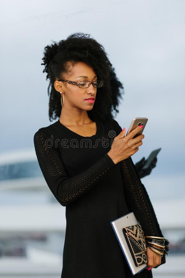 Jonge modieuze onderneemster die cellphone gebruiken stock afbeelding