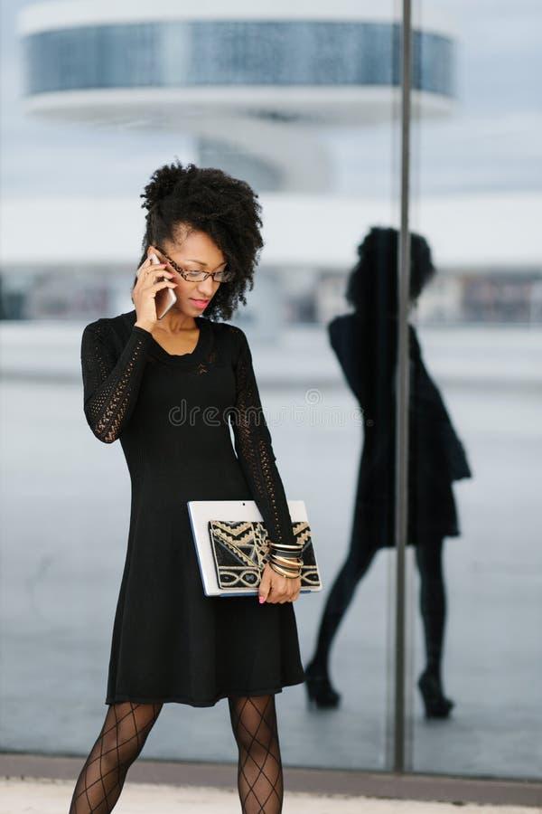 Jonge modieuze onderneemster die cellphone gebruiken stock foto's