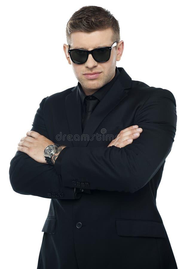 Jonge modieuze uitsmijter in een zwart kostuum, gevouwen wapens stock foto