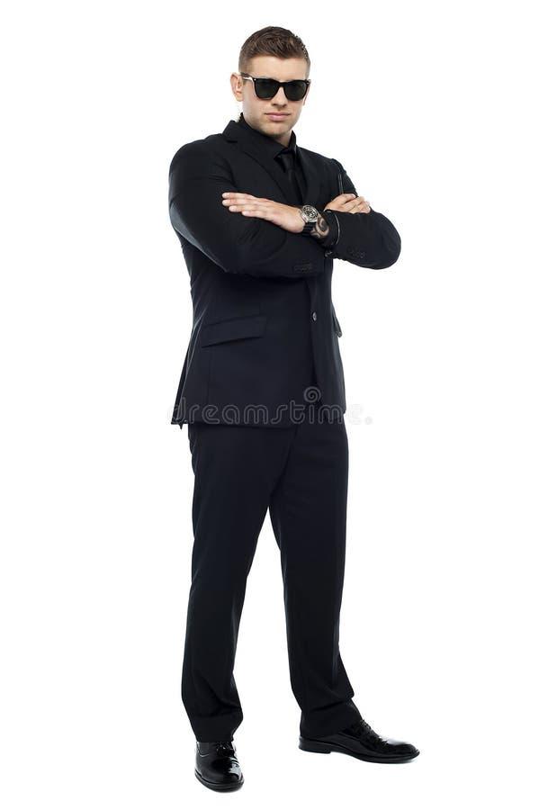 Jonge modieuze uitsmijter in een zwart kostuum, gevouwen wapens royalty-vrije stock fotografie