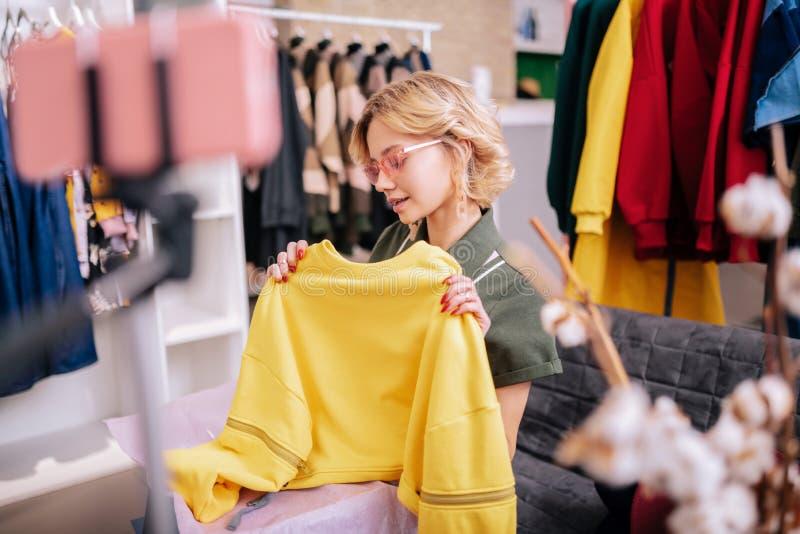 Jonge modieuze vrouw die in aardige zonnebril blog over kleren filmen royalty-vrije stock foto's