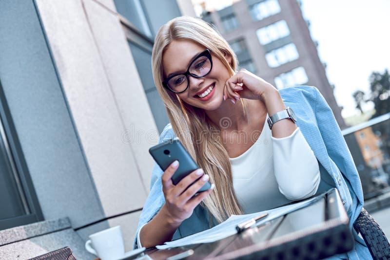 Jonge modieuze vrouw die bij smartphone in koffie babbelen stock foto's